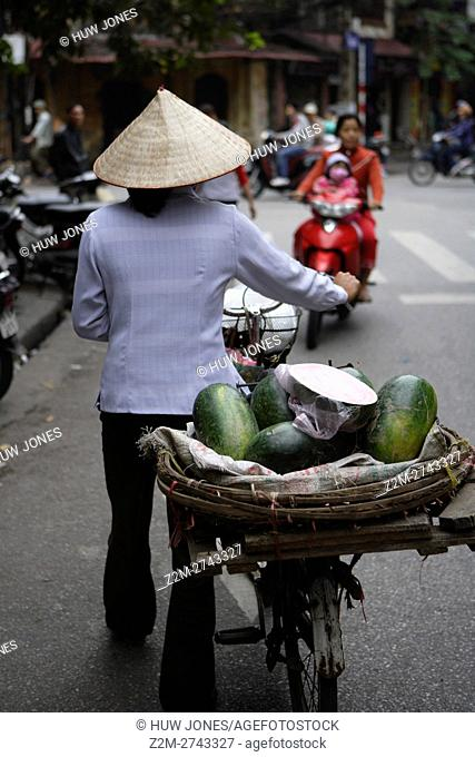 Woman pushing a bicycle with basket of vegetables, wearing a traditional Non La Hat, Old Quarter, Hanoi, Vietnam