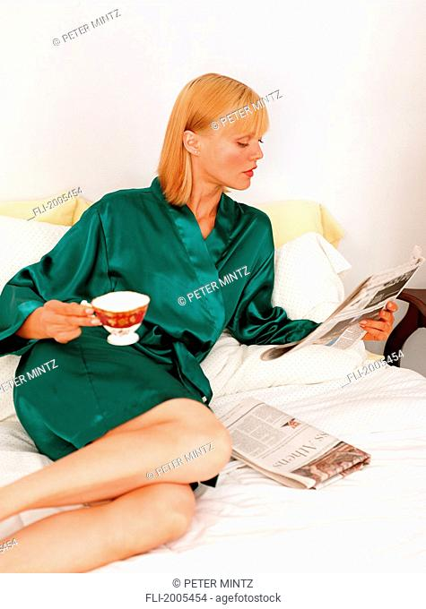 Woman In Robe Reading Paper With Cup Of Tea On Bed