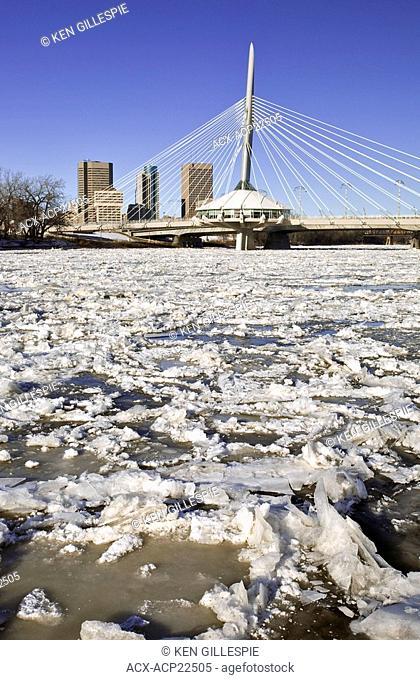 Ice forming on the Red River, Esplanade Riel Bridge and Winnipeg skyline in the background. Winnipeg, Manitoba, Canada