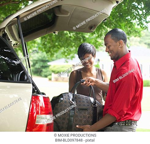 African American couple packing car for trip