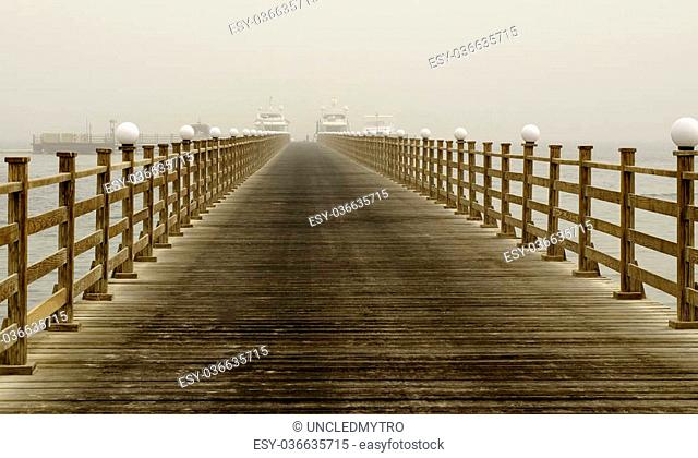 Long wooden pier into the sea in mist