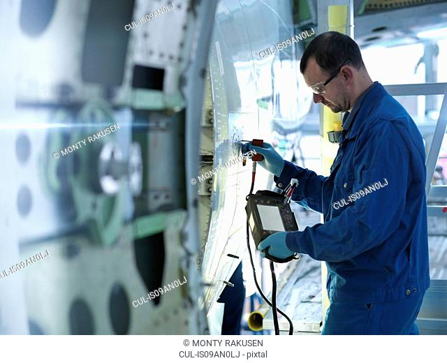 Engineer using non-destructive testing equipment on aircraft fuselage in aircraft maintenance factory