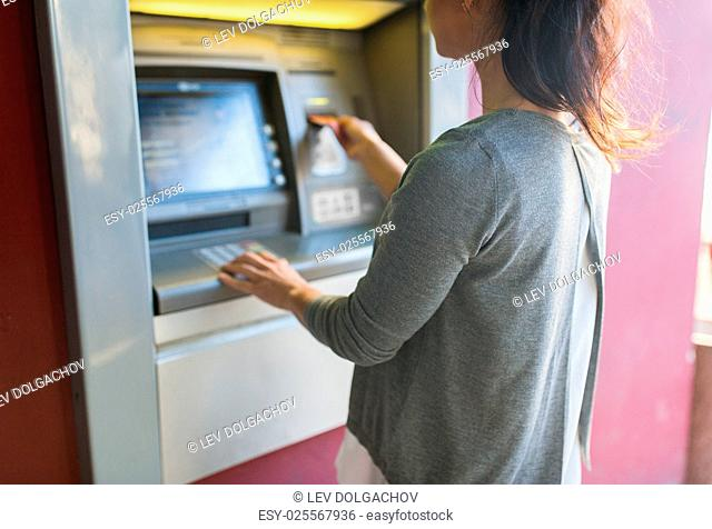 finance, money, bank and people concept - close up of woman inserting card to atm machine