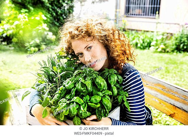 Portrait of young woman with fresh herbs in a box