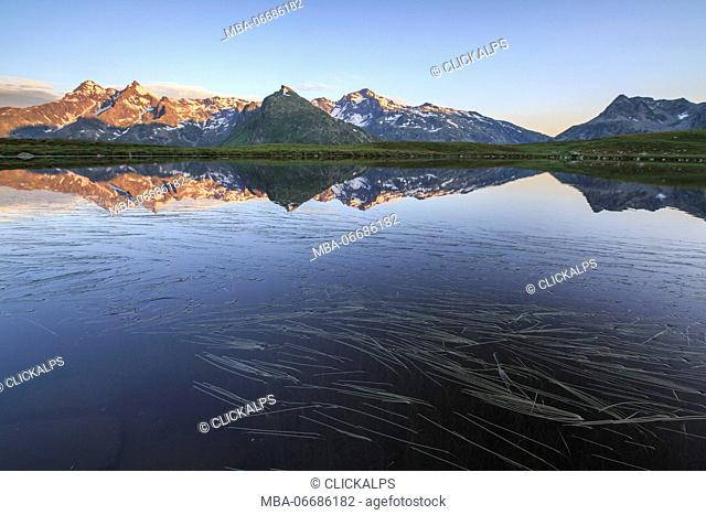 Mount Cardine and Peak Tambò are reflected in Lake Andossi at sunrise Chiavenna Valley Valtellina Lombardy Italy Europe