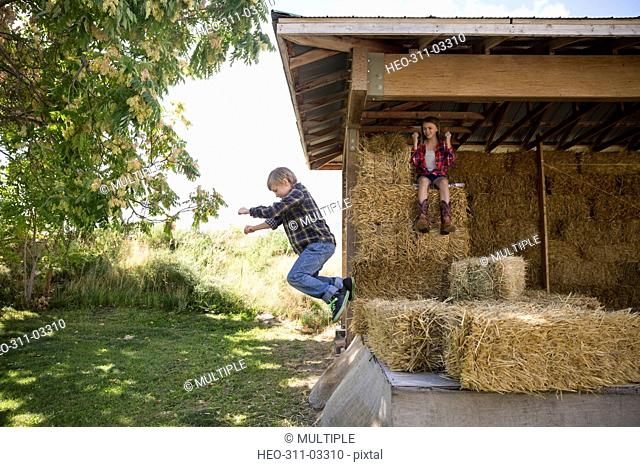 Brother and sister jumping and playing on hay bales in barn