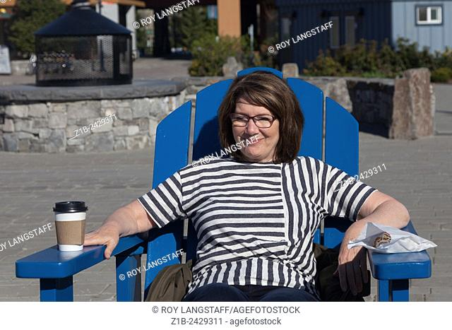 Woman resting in the sun with a coffee and a pastry breakfast snack