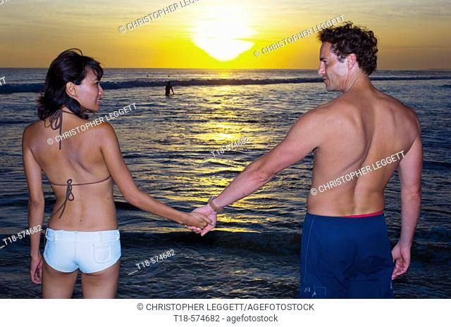 couple holding hands on beach with sunset in the background