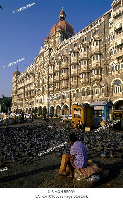 Apollo Bunder. Colaba. Taj Mahal hotel. Facade. Built 1903. Dome. Road. Man seated. Pigeons on pavement