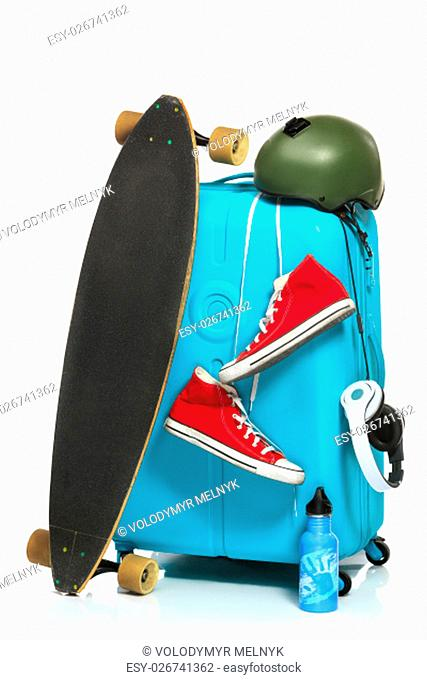 The blue suitcase, sneakers, skateboard on white background. The travel, tourism and holidays concept