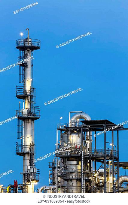 Detail of distillation towers in a chemical plant and refinery with night blue sky