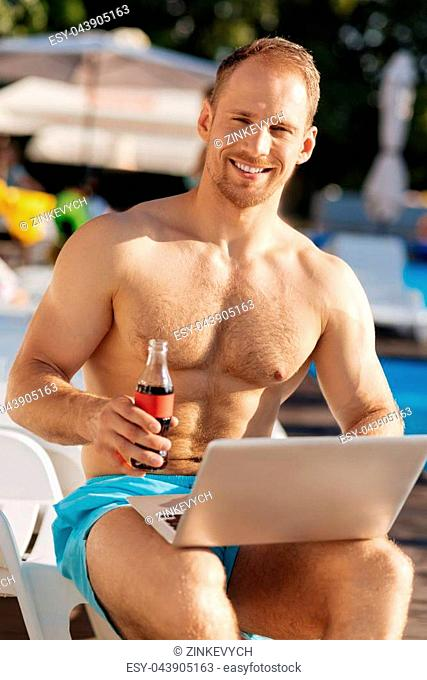 Lovely day. Strong man sitting near the swimming pool, having a laptop in his lap and holding a bottle of soda drink while pleasantly smiling at the camera
