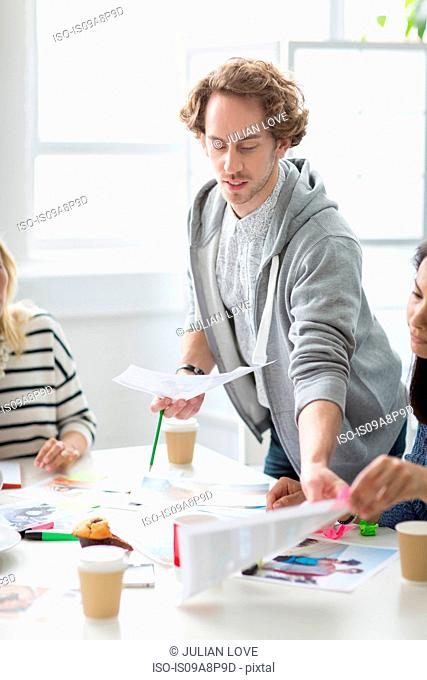 Young man showing plans in meeting in creative office
