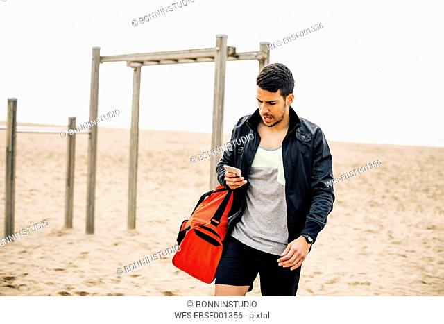 Young man looking at cell phone on the beach