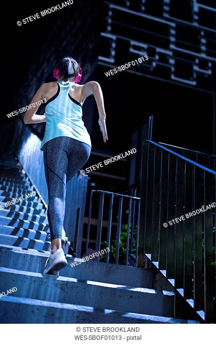 Young woman with pink headphones running upstairs in modern urban setting at night