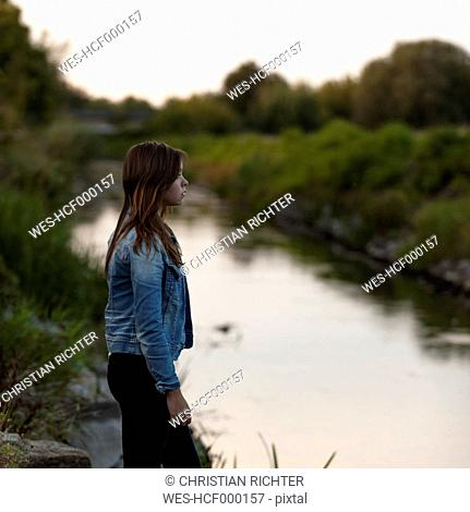 Portrait of teenage girl standing at riverside
