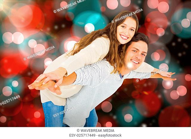 Composite image of man giving piggy back to his girlfriend