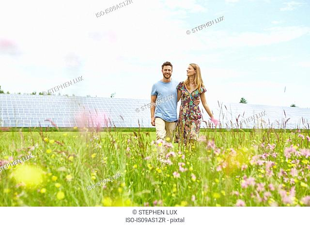 Young couple walking through field next to solar farm