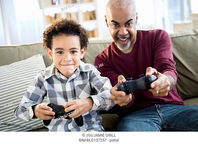 Mixed race grandfather and grandson playing video games