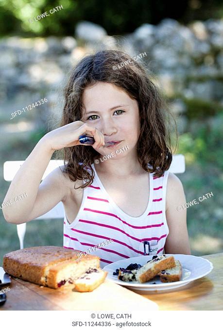 A girl eating blackberry cake in the garden