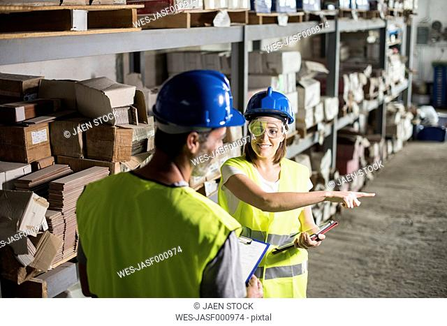 Man and woman taking stock in warehouse of construction company