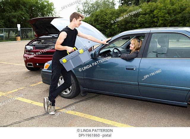 a young man helps a woman with car trouble, edmonton, alberta, canada