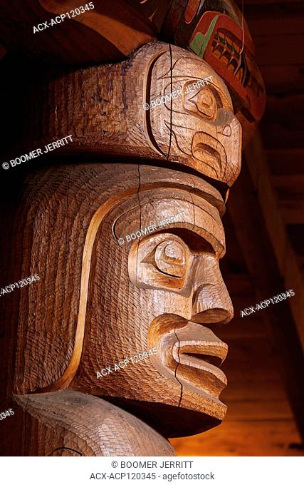A large large corner post highlights crests and figures relevant to the Wuikinuxv first nations people in their bighouse