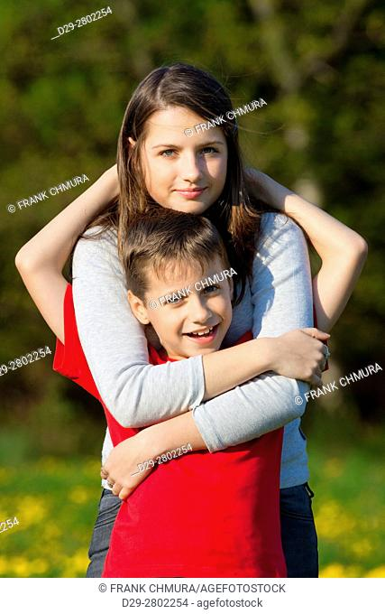 portrait of brother and sister outdoor holding each other