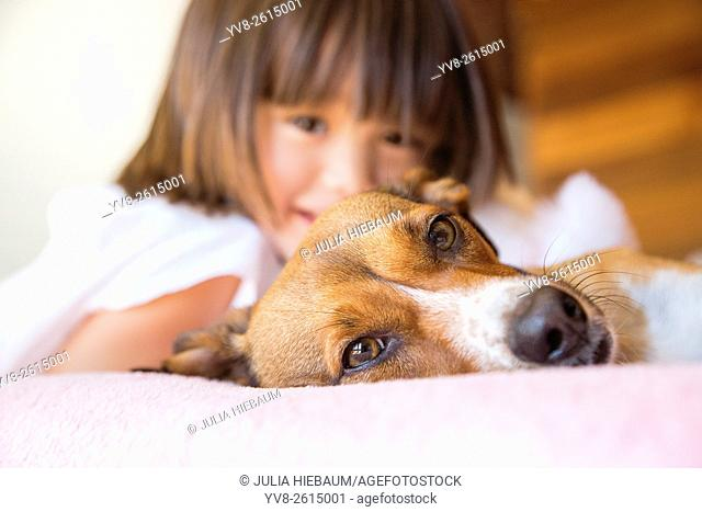 Toddler girl and her pet dog laying on the bed