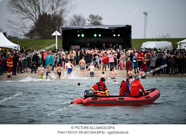 01 January 2019, Lower Saxony, Butjadingen: DLRG rescue swimmers observe the 20th traditional bathing on New Year's Day in the North Sea lagoon of Butjadingen...