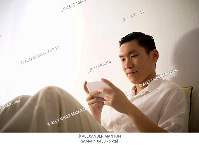 Singapore, Young man texting on sofa
