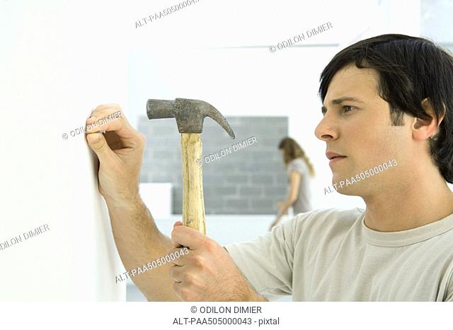 Man hammering nail into wall, woman in background