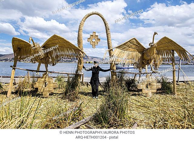 Front view of woman standing at bird sculpture on floating islands at Titicaca Lake, Puno, Peru