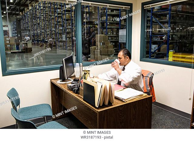Hispanic American executive working on a computer in an office in the middle of a large distribution warehouse full of racks of cardboard boxes on pallets