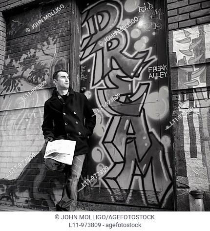 Man leaning in alleyway with newspaper, looking off