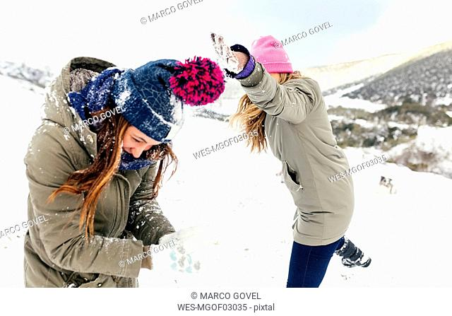 Friens having a snowball fight in the snow
