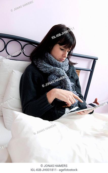 This picture shows a young caucasian woman with brown hair as she lies in her bed feeling ill or sick and surfs on the internet to check health websites