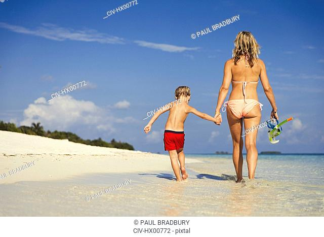 Mother and son walking on sunny tropical beach