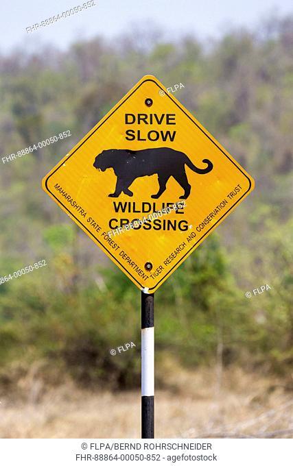 roadsign 'drive slow, wildlife crossing' with tiger, near Tadoba National Park, Maharashtra, India, April