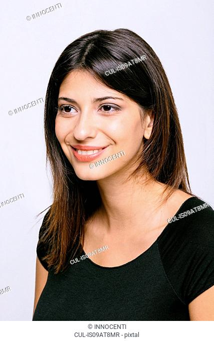 Head and shoulder portrait of young woman looking away smiling