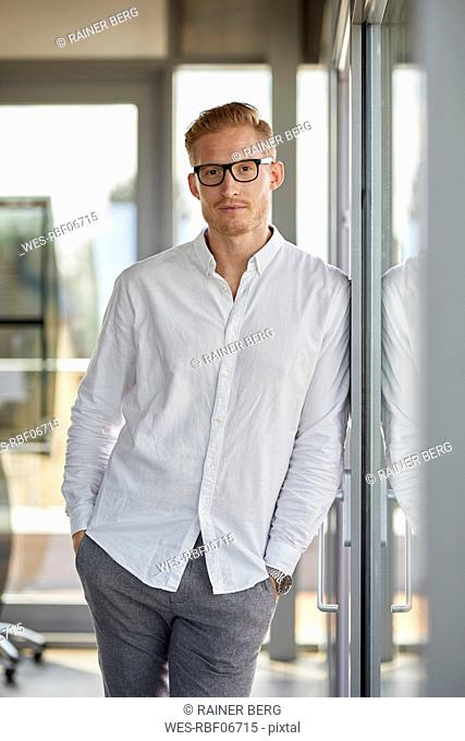 Portrait of confident businessman in office leaning against window