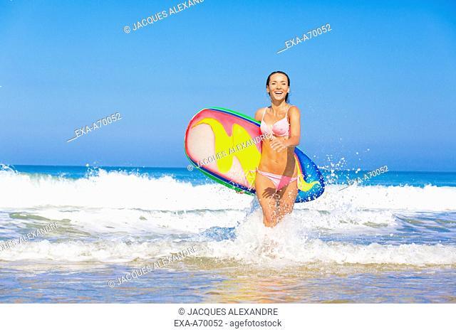 woman runs at beach with surfboard