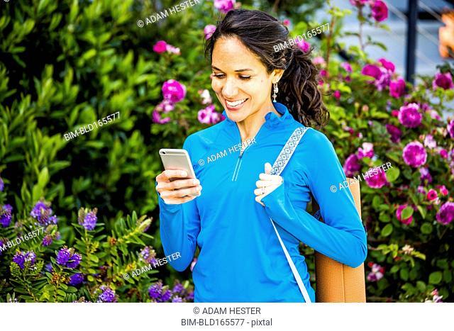 Hispanic woman using cell phone in garden