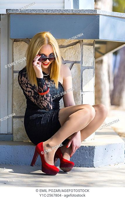 Fanciful teen-girl sitting sideways and peeking over sunglasses