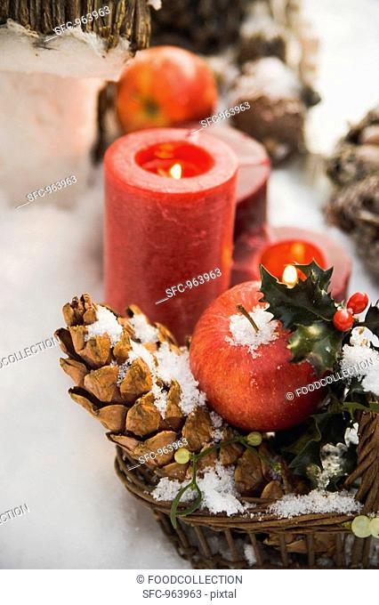 Christmas decorations: apples, cones and candles in snow