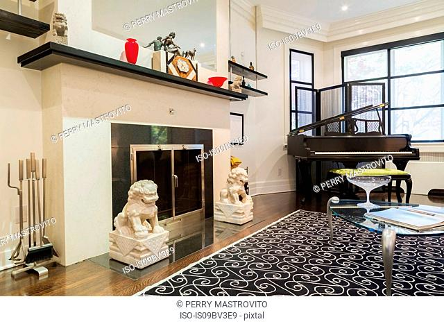 Wood-burning fireplace, grand piano, glass top and silver metal coffee table in living room, wood plank flooring and rug