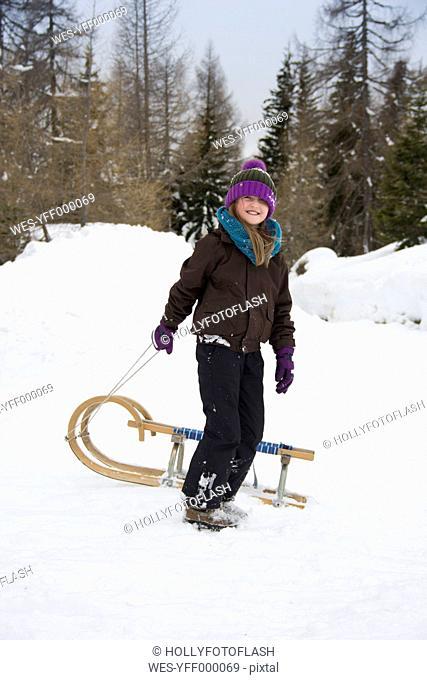 Austria, Carinthia, Gmuend, smiling girl pulling sledge