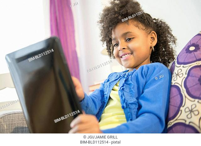 African American girl using tablet computer on sofa