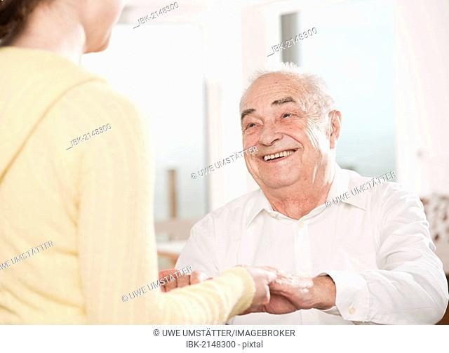 Young woman taking care of an elderly man