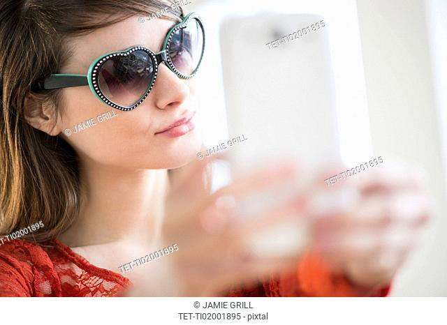 Young woman wearing heart shaped sunglasses